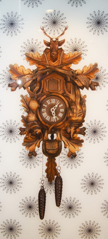 An up close photo of the wood carved cuckoo clock annealed on an interlayer of white, back-painted safety glass.